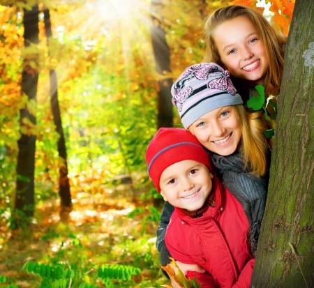 hermanos jugando: Niños felices que se divierten en el Parque de otoño. Al aire libre