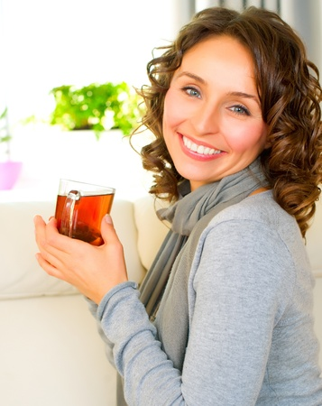tee: Beautiful Young Woman drinking hot tea