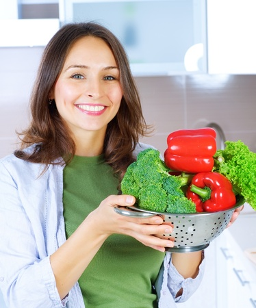 Beautiful Young Woman cooking fresh Vegetables. Dieting Concep  photo