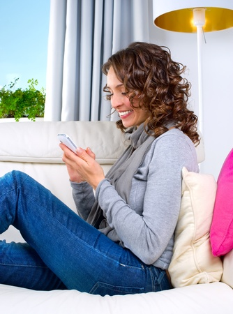 Young Woman with Mobile Phone at Home  Stock Photo - 11131045