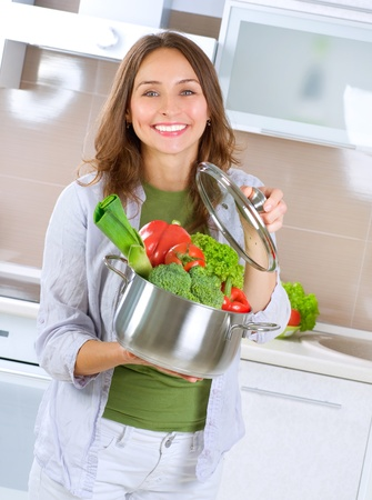 Beautiful Young Woman cooking fresh Vegetables photo