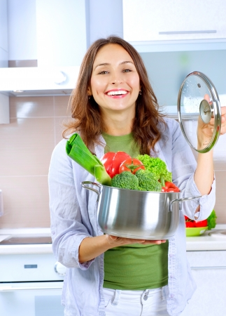 woman cooking: Beautiful Young Woman cooking fresh Vegetables
