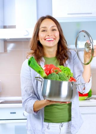 cuisine: Belle Jeune Femme cuire des l�gumes frais Banque d'images