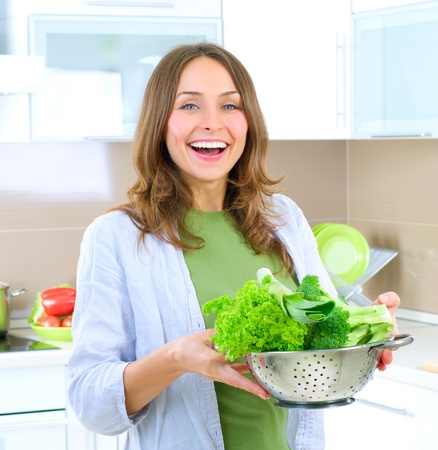 boiling pot: Beautiful Young Woman cooking fresh Vegetables