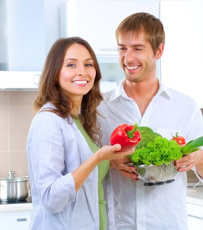 Young happy couple cooking together at home kitchen  photo
