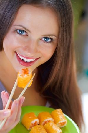 model fish: Beautiful Young Woman Eating Sushi. Diet  Stock Photo