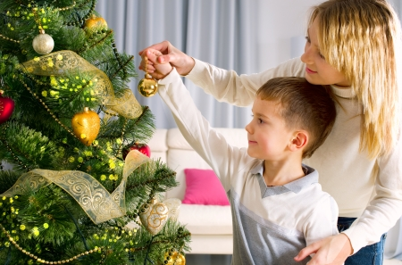 two children: Kids decorating a Christmas tree with baubles in the living-room Stock Photo