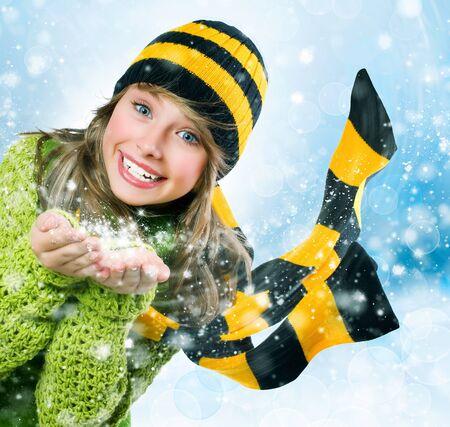 Christmas Girl. Winter Teenage girl Blowing Snow photo