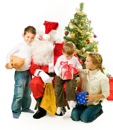 Santa Claus giving Christmas gifts to children photo