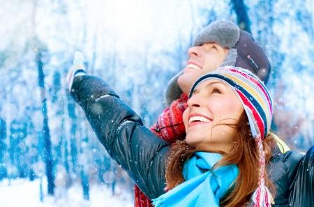 ropa de invierno: Pareja joven feliz en el Parque de Invierno se divierten. Familia al aire libre