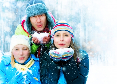 snow woman: Family Outdoors. Happy Family Blowing Snow  Stock Photo