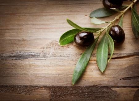 foglie ulivo: Olive su uno sfondo di legno