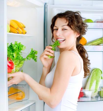 Joven y bella mujer cerca de la nevera con la comida sana