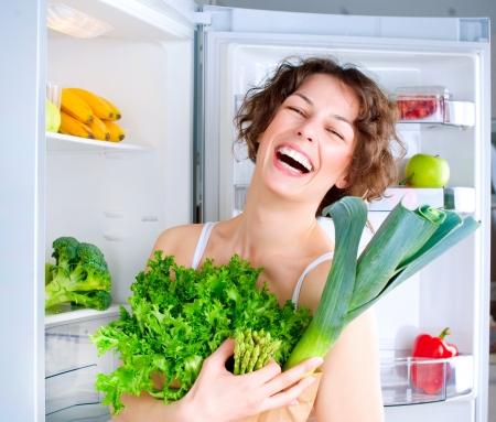 dieta sana: Joven y bella mujer cerca de la nevera con la comida sana Foto de archivo