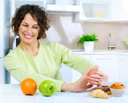 comidas saludables: Mujer Joven Hermosa elegir entre frutas y dulces Foto de archivo