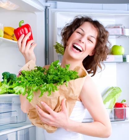 refrigerador: Joven y bella mujer cerca de la nevera con la comida sana Foto de archivo