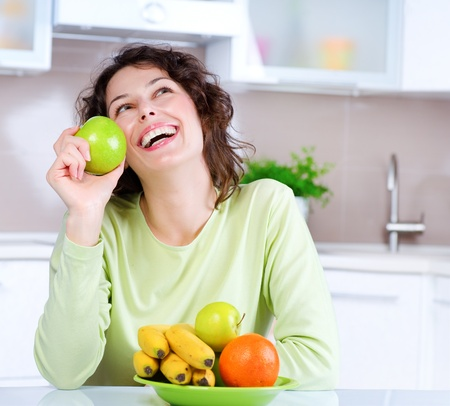 Dieting concept  Laughing Young Woman Eats Fresh Fruit  Stock Photo - 13064537