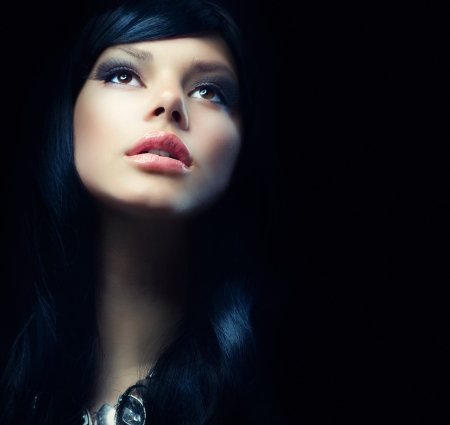 make up eyes: Beautiful Brunette Girl over Black Background  Darkness