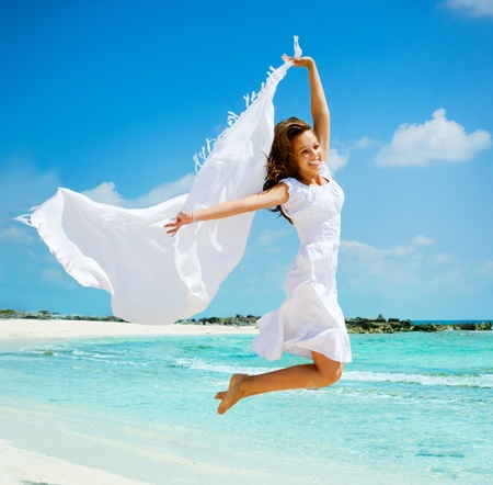 Krásná dívka s bílou šátek skákání na pláži