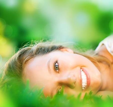 s úsměvem: Jarní dívka v zelené trávě