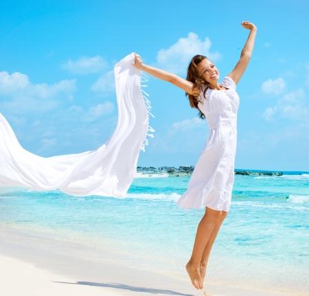 해변에 흰색 스카프 점프와 함께 아름 다운 소녀