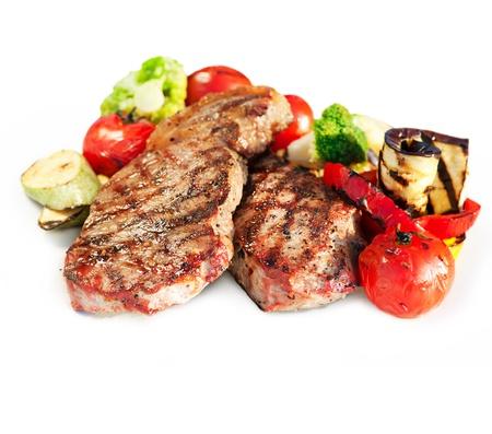carne asada: Bistec a la parrilla con vegetales sobre fondo blanco Foto de archivo
