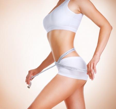 허리의 잘룩 한 선: 그녀의 허리의 잘록한 곳 다이어트 퍼펙트 슬림 바디를 측정하는 여자