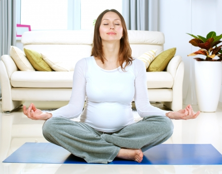 Beautiful Pregnant Woman Doing Yoga at Home photo