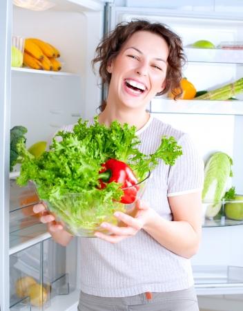 alface: Mulher nova bonita perto da geladeira com alimentos saud�veis