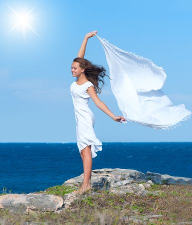 Freedom Concept  Girl with White Scarf standing on the Rock  photo