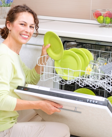 inserting: Dishwasher  Young woman in the Kitchen doing Housework  Wash-up