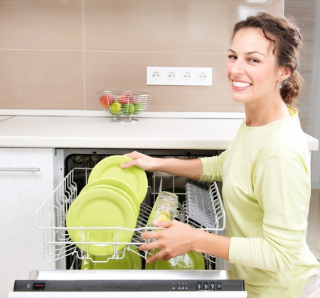 dishwasher: Dishwasher  Young woman in the Kitchen doing Housework  Wash-up