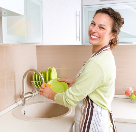 Dishwashing  Happy Young Woman Washing Dishes photo