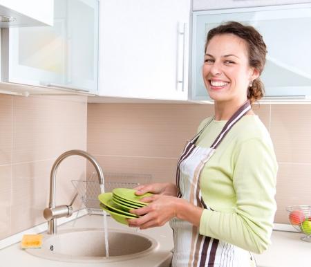 ama de casa: Lavavajillas Happy joven lavando platos Mujer