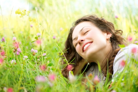 at resting: Beautiful Young Woman lying in Meadow of Flowers  Enjoy Nature Stock Photo