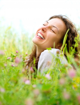 woman happy: Beautiful Young Woman lying in Meadow of Flowers  Enjoy Nature Stock Photo