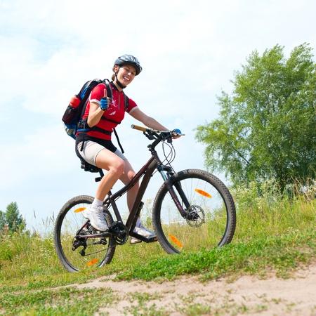 cyclist: Gelukkige Jonge Vrouw rijdt fiets buiten Gezonde Levensstijl