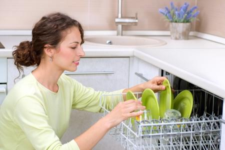 washup: Lavastoviglie giovane donna in cucina facendo pulizie Lavare-up