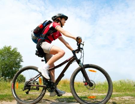 cyclist: Gelukkige Jonge Vrouw rijdt fiets buiten Healthy Lifestyle