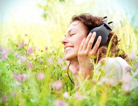 audifonos: Hermosa mujer joven con auriculares Disfrute de m�sica al aire libre Foto de archivo