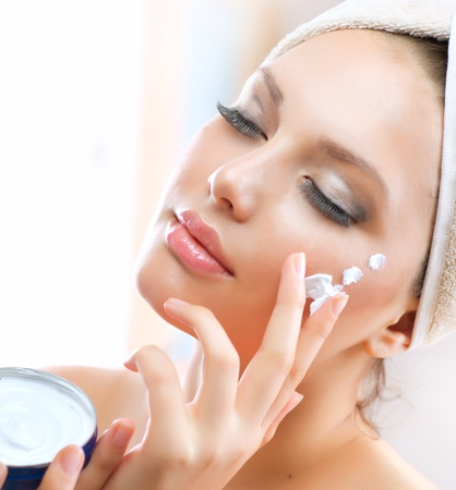Beautiful Young Woman applying facial moisturizing cream photo
