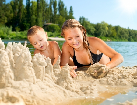 sisters: Happy kids Having Fun at the Beach in summer  River  Stock Photo