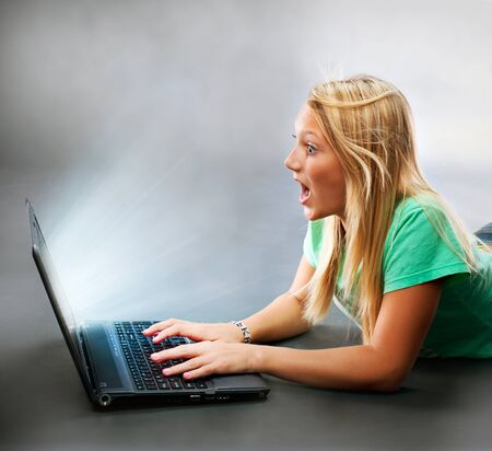 Surprised Girl With a Laptop  Working on Computer  photo