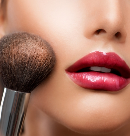 mujer maquillandose: Maquillaje en Polvo blanco cosmético para la piel pincel perfecto