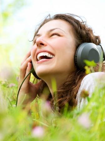 actief luisteren: Mooie Jonge Vrouw met hoofdtelefoon Outdoors Geniet van muziek