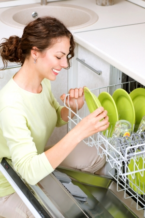 clean dishes: Dishwasher  Young woman in the Kitchen doing Housework  Wash-up