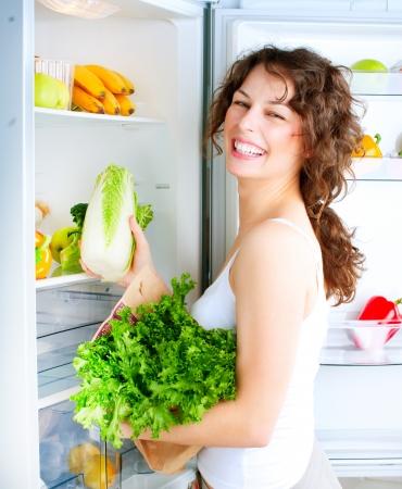 alimentos saludables: Mujer joven hermosa cerca de la nevera con alimentos saludables