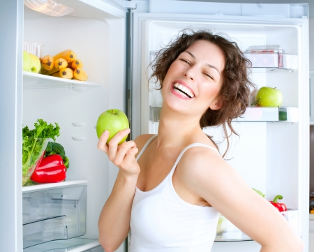 refrigerator: Beautiful Young Woman near the Refrigerator with fresh apple  Stock Photo