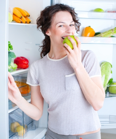 woman apple: Beautiful Young Woman near the Refrigerator with fresh apple  Stock Photo