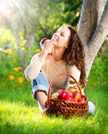 canastas con frutas: Feliz mujer joven sonriente que come manzana org�nica en el Huerto Foto de archivo